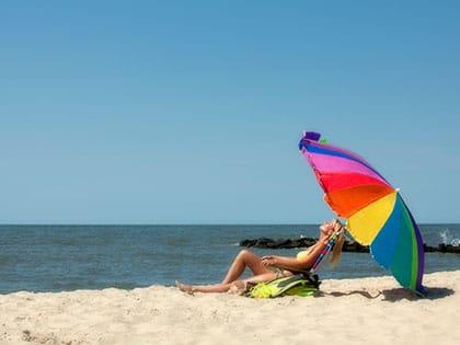 woman on beach with umbrella